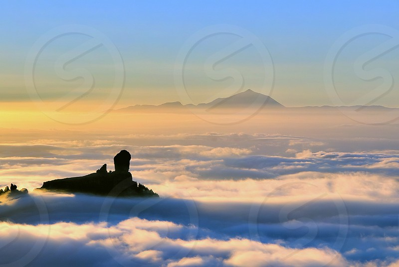 Roque Nublo (foregorund) and volcano Teide (background) over a sea of clouds at Canary Islands photo