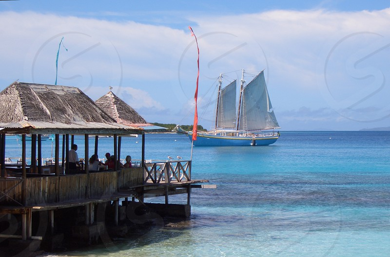 Sailboat on blue tropical waters of the Carribean with an over-water bungalow hut in foreground. photo