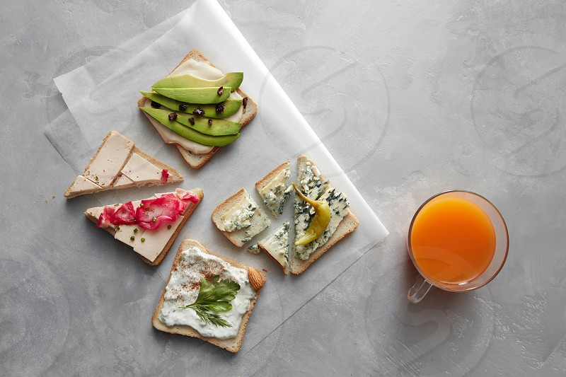 Top view of different kinds of sandwiches for tasting or having break isolated on table. Glass of orange juice not far from. Sandwiches with cheese avocado etc. photo