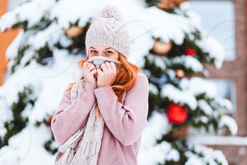 Young woman in front of the Christmas tree outdoors photo