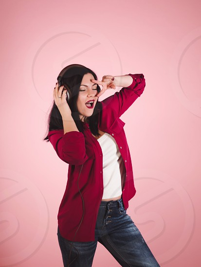 Joy and music. Colorful studio portrait of happy young brunette woman with earphones is dancing and singing on pink background. photo