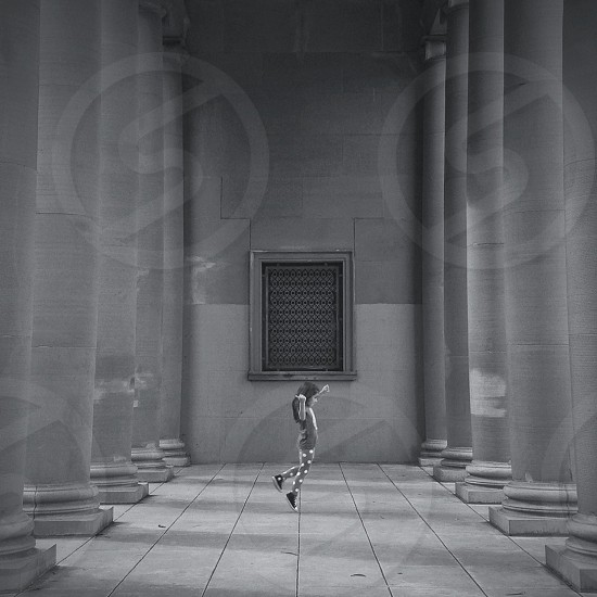girl jumping at the museum grayscale photo
