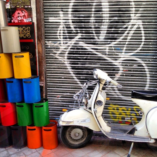 white vespa scooter parked near tagged garage door and colorful bucket stack photo