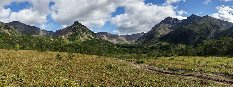 Beautiful panorama mountain landscape of Kamchatka Peninsula: early autumn view of Mountain Range Vachkazhets with forest slopes of hills glade grass covered and clouds in blue sky on sunny day. Eurasia Russian Far East Kamchatka Region. photo
