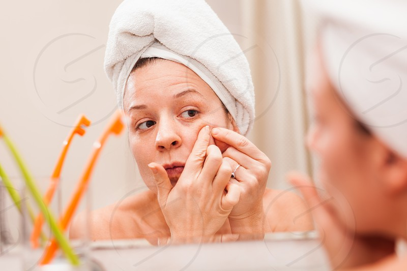 Young woman squeezing acne on her face in the bathroom photo