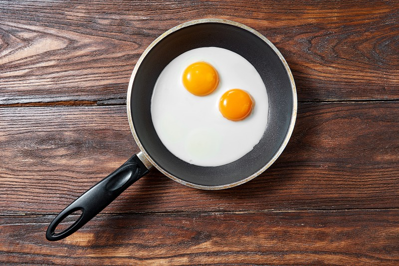 Fresh fried eggs with two yellow yoks in a frying pan on a wooden background place for text. Breakfast healthy food concept. Flat lay. photo