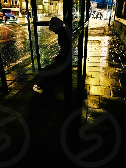 Person Waiting In Rain At Bus Stop photo