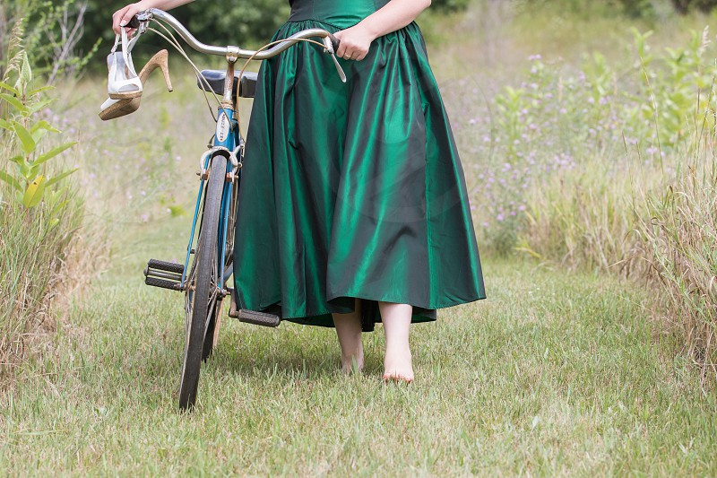A woman in a green dress pushes a bike through a field of wildflowers.  Release available upon request. photo