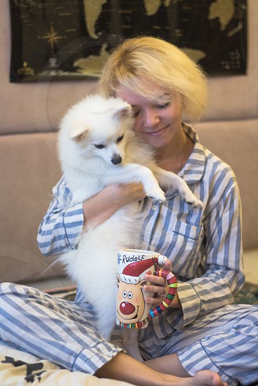 Owner with white dog sit in bed photo