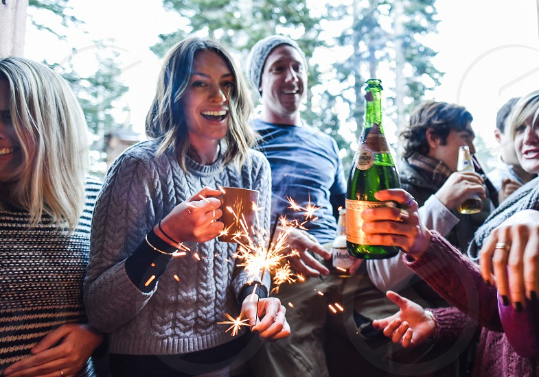 young adults celebrate champagne sparkler photo