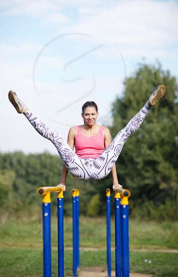 Athletic attractive young female gymnast exercising on parallel bars balancing on her hands with both her legs raised high in the air photo