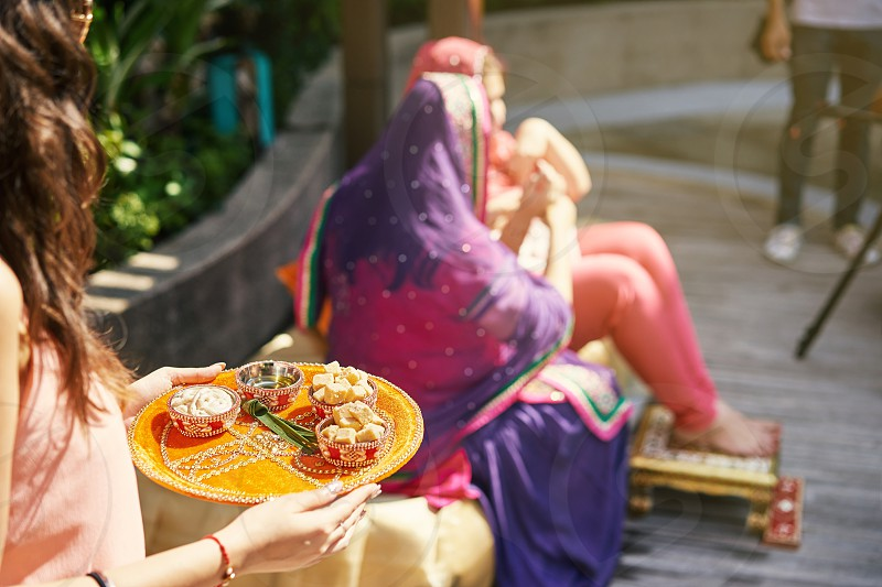 The indian women holding the yellow tray of prayer items during thread ceremony (puja pooja) of Indian wedding with the bride and mother blurry in background photo