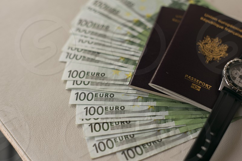 close up of one hundred euro bank notes and passport photo