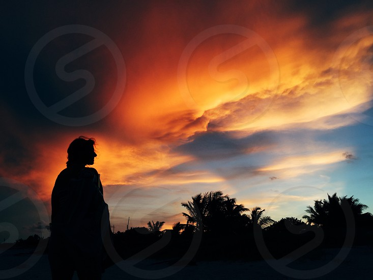Silhouette of a woman watching a tropical sunset in Cancun photo