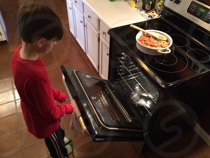 person opening a black induction electric oven photo