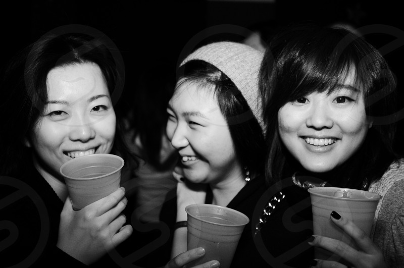 three woman holding brown plastic cup photo