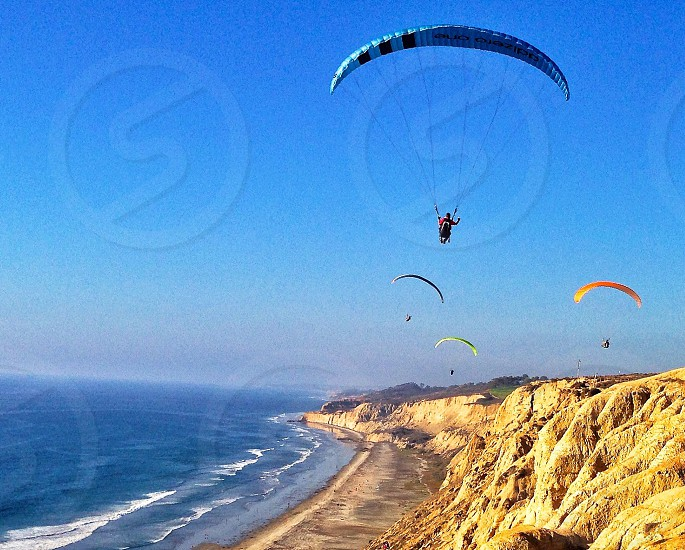 Parasailing CA Torres pines ocean blue sails rocky cliffs freedom fly flying photo