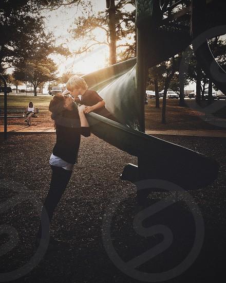 A little boy kissing on a slide. photo