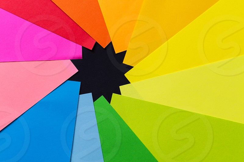 Vibrant color paper stacked in circle forming black multi point star photo