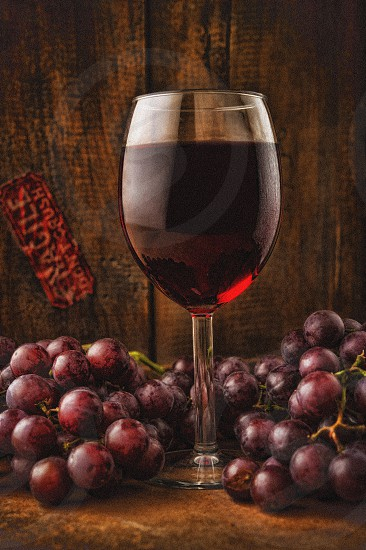 Glass of red wine surrounded by grapes photo