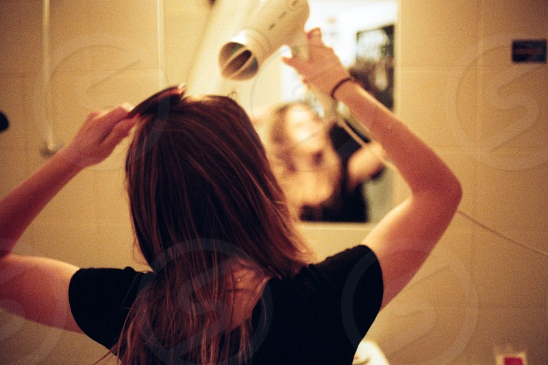 woman wearing black t shirt using hair dryer standing in front of mirror  photo