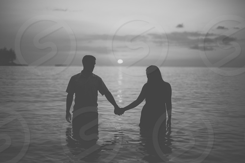 man and woman holding hands in water photo