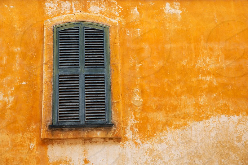 Ciutadella Menorca wooden shutter window on grunge yellow downtown wall at Balearic islands photo