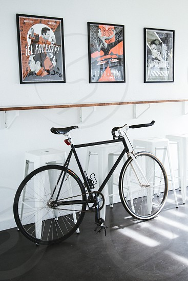 black road bicycle leaning on white bar stools near white wall with 3 framed arts photo