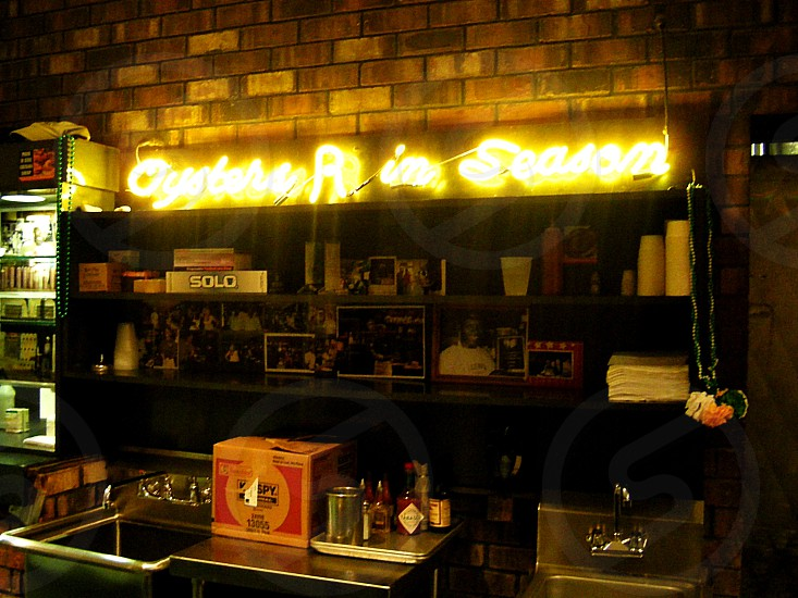 "Bar with neon "" Oysters in Season""  in yellow photo"