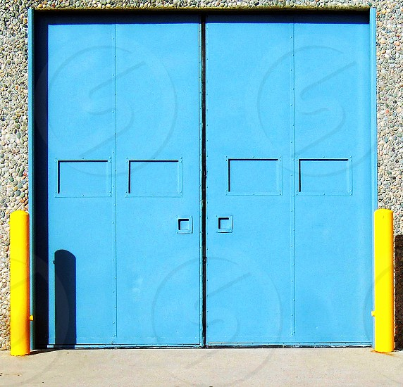 Double aqua blue industrial metal doors have yellow posts next to them in an industrial area photo
