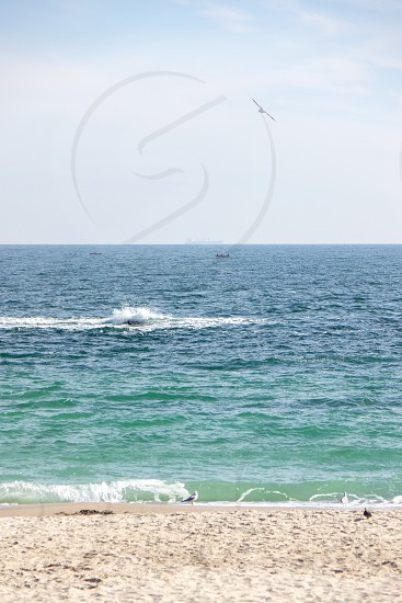 Beautiful summertime seascape with waves birds small boats on a soft cloudy sky. photo