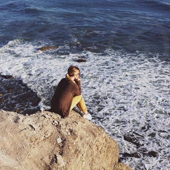 woman sitting on rock beside seashore photography photo