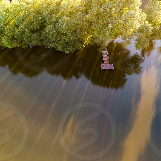 aerial view of the lake with wooden bridge for fishing surrounded by forest. Photo by drone photo