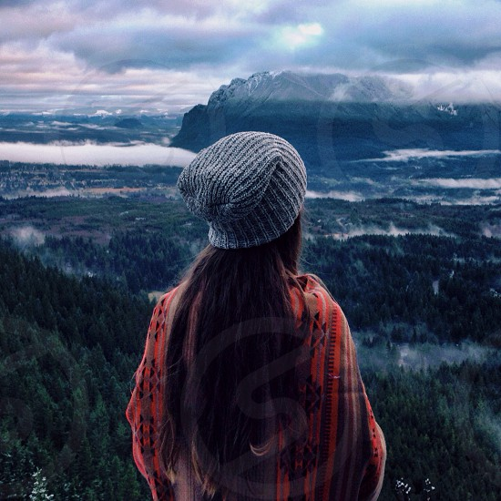 woman in grey beanie standing on a cliff photo