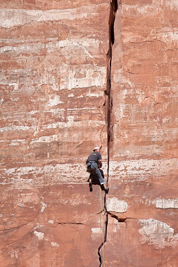 Man climbing sheer rock face in Zion National Park photo