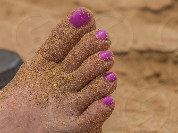 Surf and sand between her toes photo