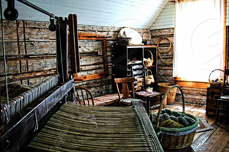 A large weaving loom is in a rustic room filled with wool. photo