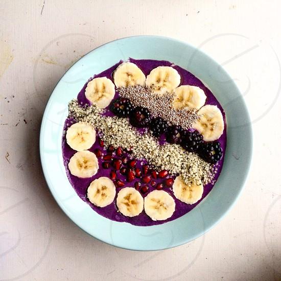 sliced banana blackberries and purple cream in a white ceramic bowl photo