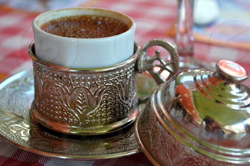 Beautiful silver coasters with a lid for a cup of coffee in a Turkish cafe. photo