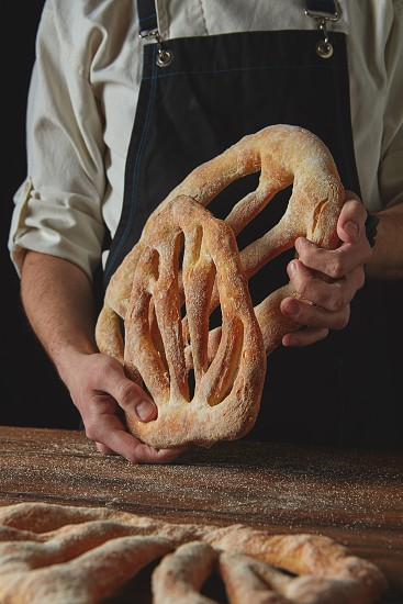 Freshly delicious bread baker holds in hands on a dark background photo