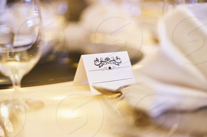 Selective focus mock up for white label with ornament art for name tag on the dinner table with bokeh and bokeh blurry foreground and background photo