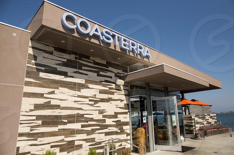 orange patio umbrellas outside gray concrete store with coasterra sign photo