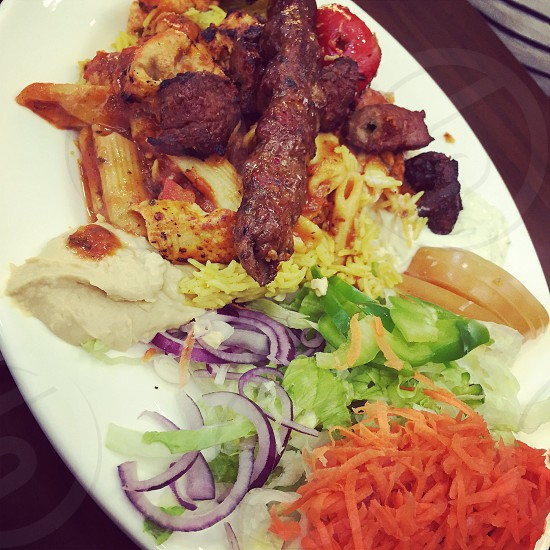 Arab/Lebanese / Indian Food: mix grill of kebabs  chicken tikka lamb tikka and spicy rice with fresh salad photo