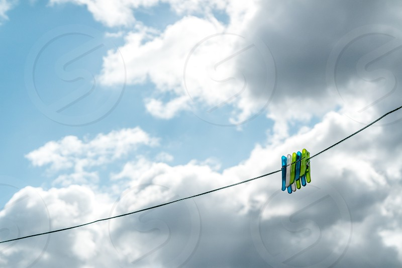 Clothes pegs on a line with a beautiful blue sky in the background and fluffy white clouds photo