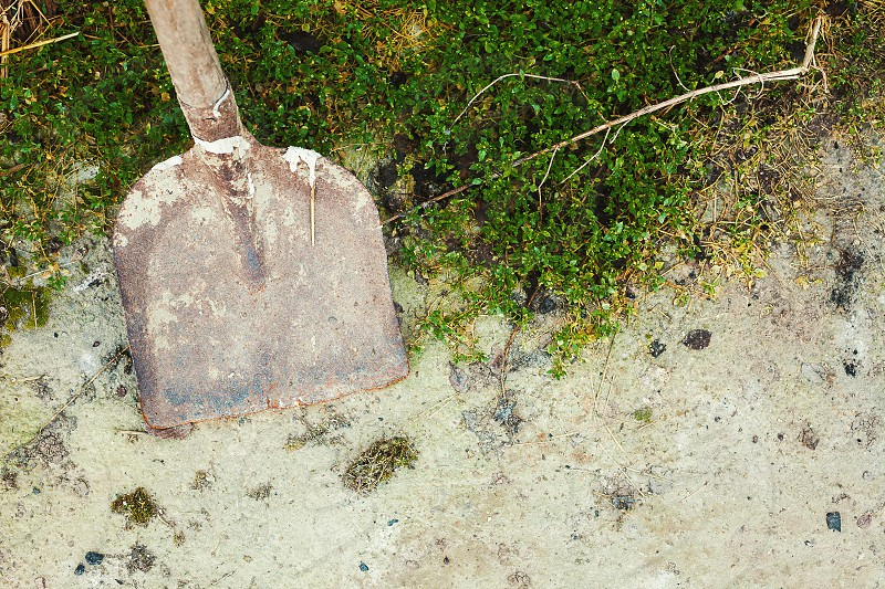 Old and dirty shovel on asphalt scene from a village life.  photo