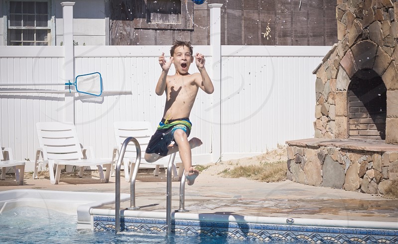 boy in black and green shorts jumping on pool photo