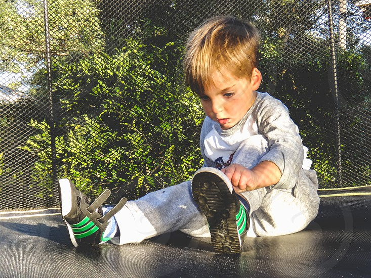 little boy sitting on a trampoline putting on his sneakers  photo