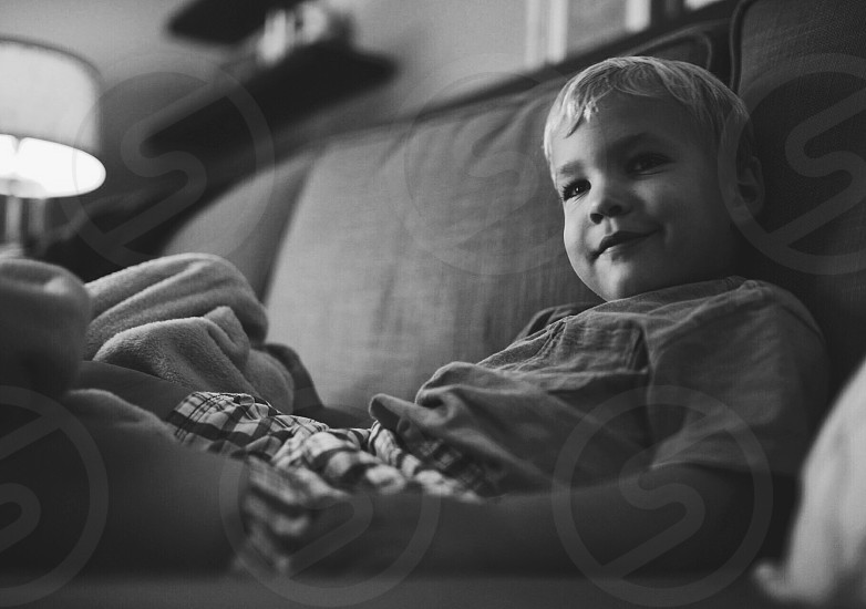 grayscale photography of boy sitting on sofa photo