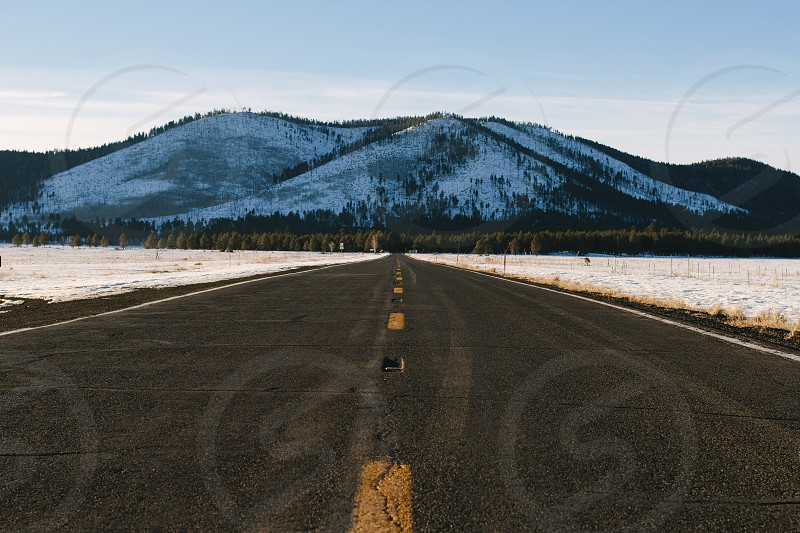 view of gray and yellow empty road and blue and white mountains photo