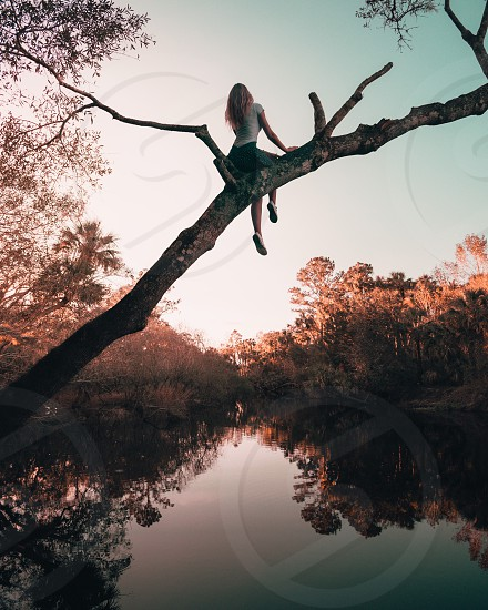 Fairytale esque shot of a girl sitting over a beautiful river at sunset photo